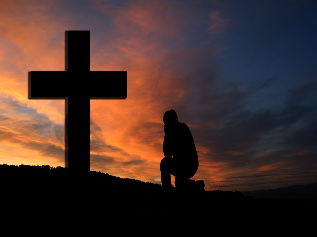 Is Confession Good for the Soul? A person kneeling in front of a cross, silhouetted by a sunset