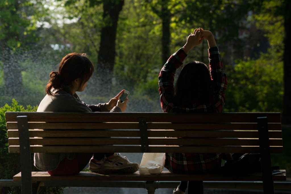 Rest for Your Soul_two women on park bench, one looking at phone, one stretching arms overhead