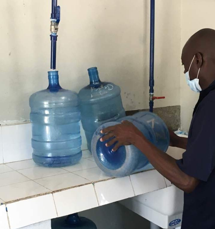 Why Do We Work_Haitian man filling water from clean water facility