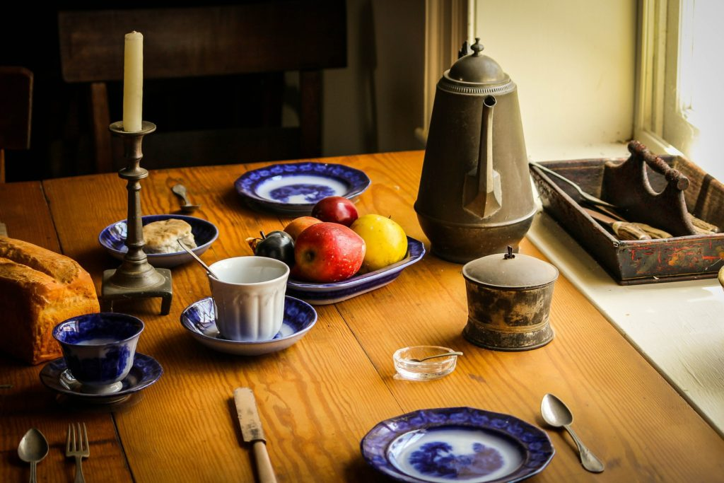Hospitality: A Call to Open Hearts and Homes_still life of farmhouse table with two blue place settings, coffee cups, fruit, pitcher