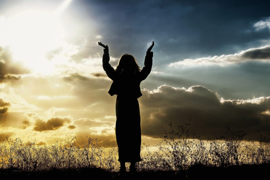 Where Do You Turn When You Need Help_woman in robe, arms stretched toward heaven, shadowed against a radiant sky