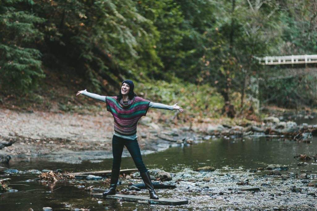 2 Surprising Ways to Change the World_young woman standing on log in creek, arms outstretched, happy, looking slightly up