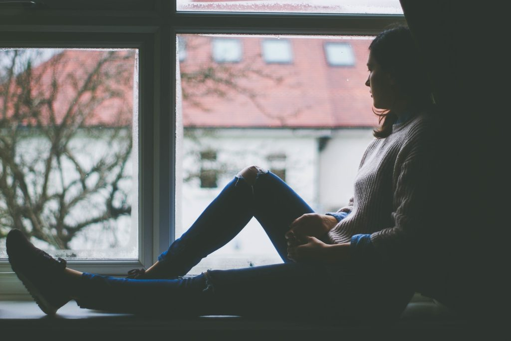 How to Handle Your Burdens_young woman sitting on window sill, looking out window to gray day