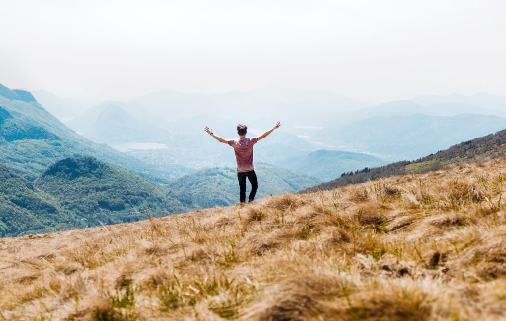 What to Do When You Don't Get What You Want_man standing on hillside overlooking mountains, hands lifted high