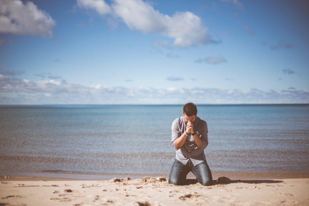 When God Reveals Deep and Hidden Things_man kneeling on seashore, praying