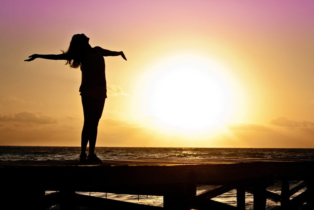 When You See the Deliverance of the Lord_woman standing on boardwalk over water, arms outstretched, chin toward sky, silhouetted against the sunset