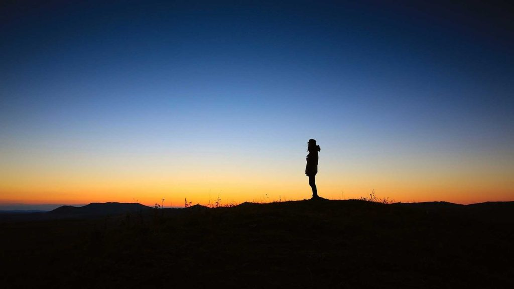 When the World Feels Broken_A Way to Be Still_lone person silhouetted, standing on top of dark ridge, looking at sunset