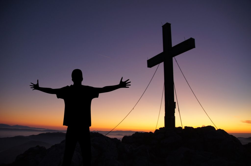 When Your Worst Day Becomes the Best Gift Ever_Man with arms outstretched standing in front of a cross, all in silhouette
