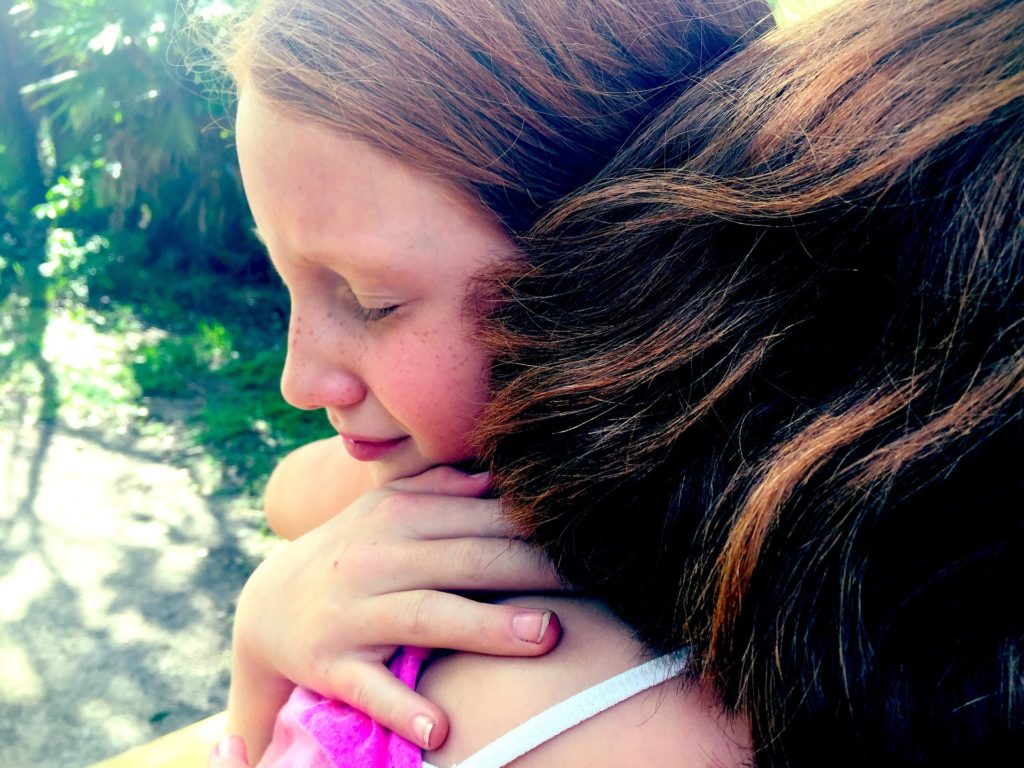 Young girl, eyes closed, hugging a girl or woman