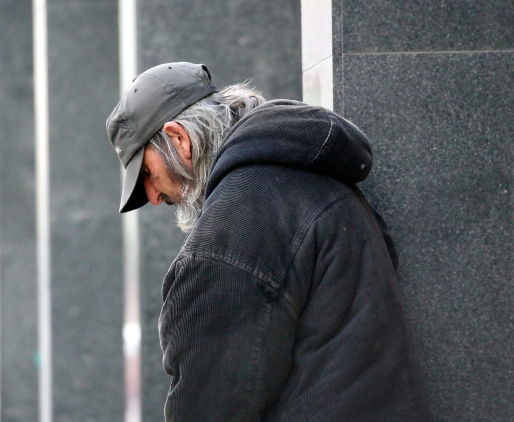 Caucasian man with gray hair, gray ball cap, gray coat, by gray wall, looking downtrodden