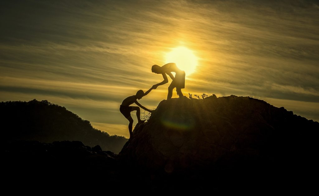 Silhouette of teen boy on top of a mountain or plateau reaching with one hand to pull another teen boy up the mountain
