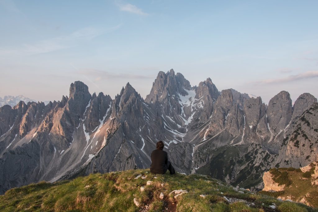 View from back of man in black jacket, sitting on green ridge, looking at rocky, craggy mountains
