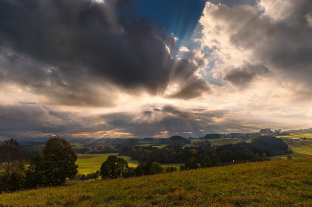 Landscape with green fields and trees in the foreground, sunbeams shining through clouds in the distance