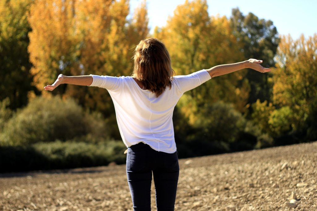 Woman in white blouse, blue jeans, facing away from camera, arms outstretched, looking at trees, sun shining