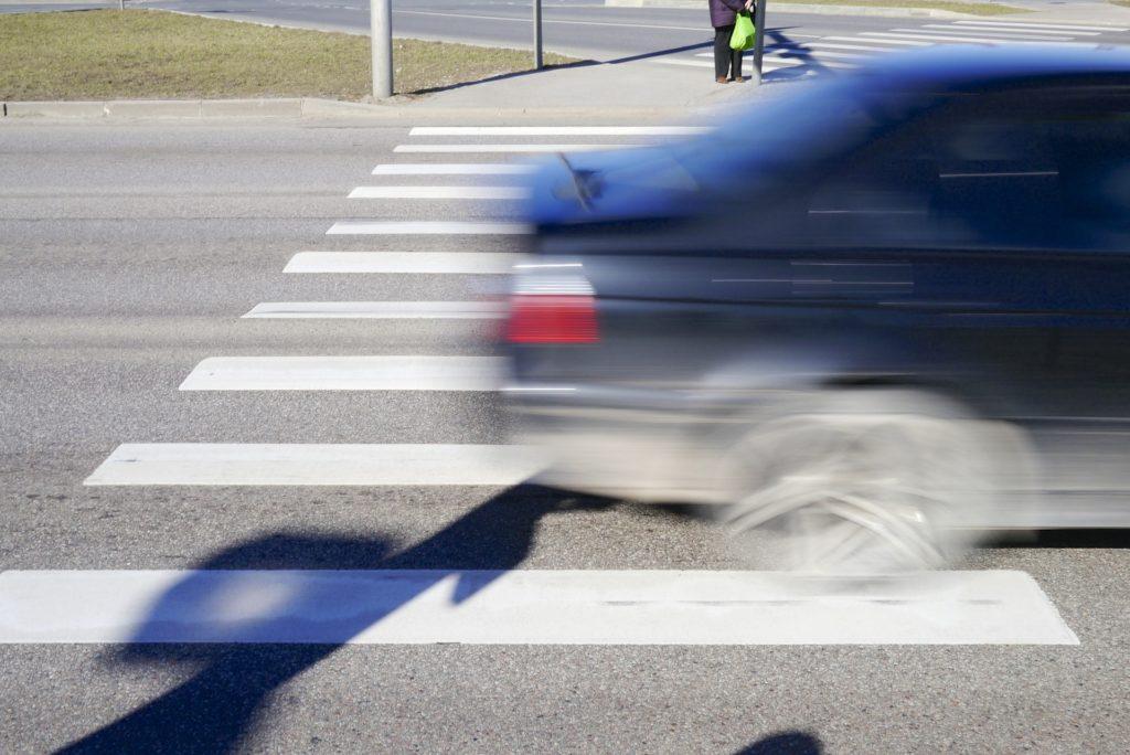 Blurred blue car speeding through crosswalk, only back third of car is shown