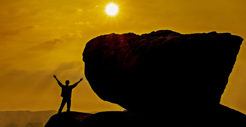 Silhouette of man with arms raised, looking at sun, standing next to enormous rock, double his height