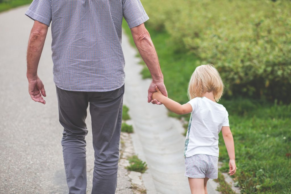 A view from the rear of a little girl holding her father's hand, walking on the side of a road