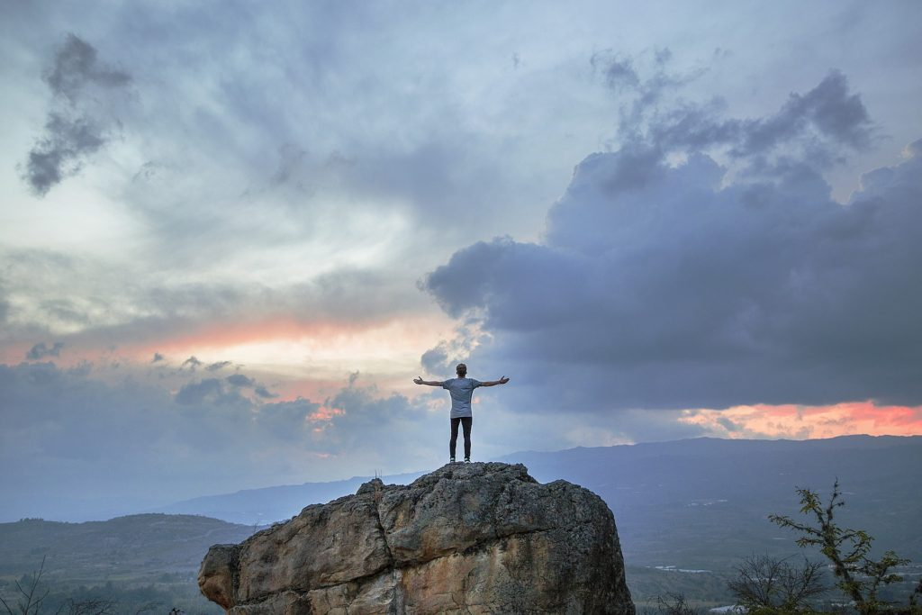 Hiker on top of large rock, arms outstretched, looking up to sky of variety of blue colors