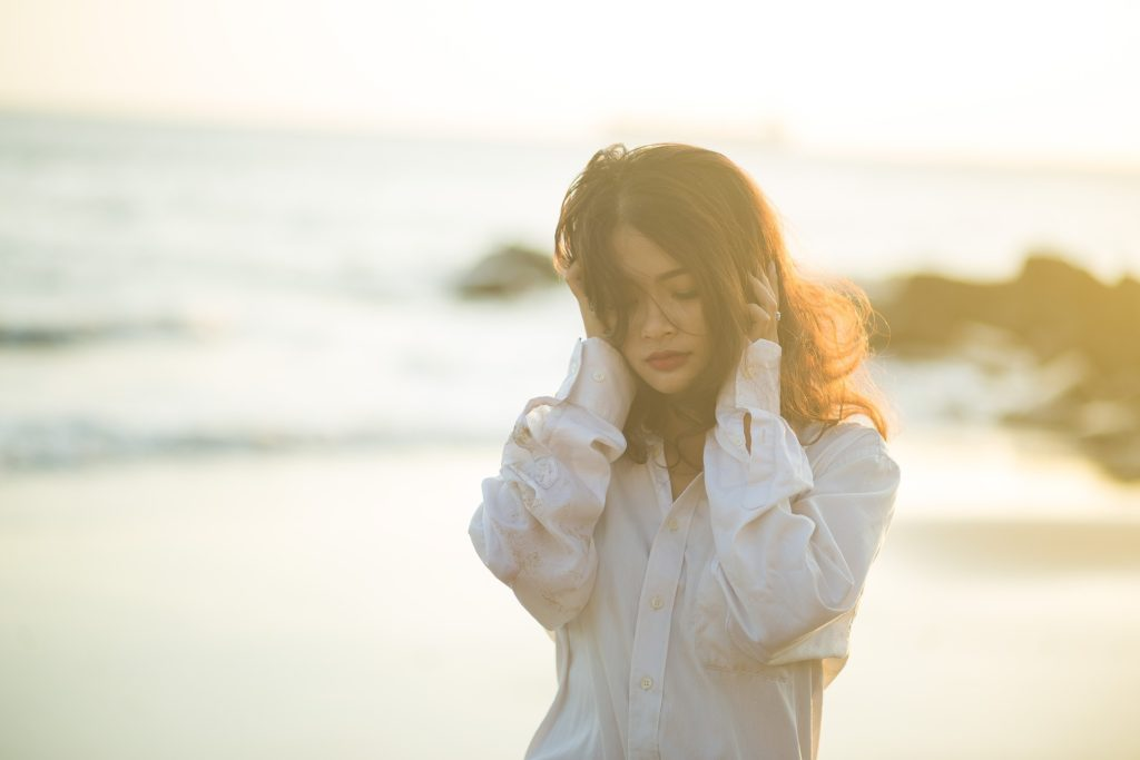 Woman in long-sleeved blouse walking by ocean, hands to head, eyes downcast, sad