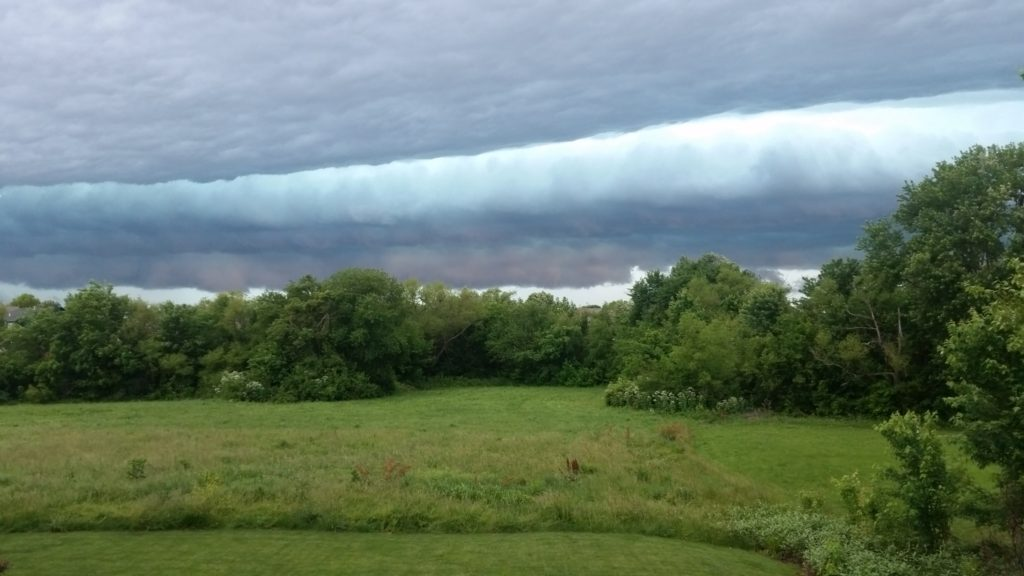 A roll cloud, turquoise and dark blue, coming in over a green treeline with a field in the foreground