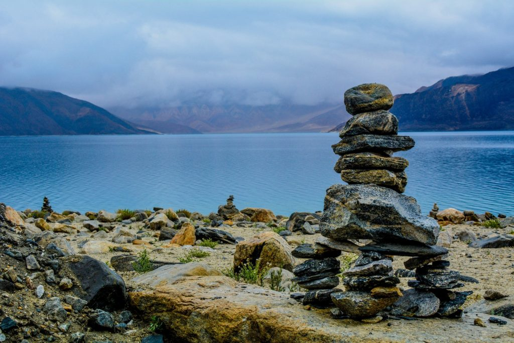 A pile of rocks, with 3 piles as the base and one pile stacked vertically on top the base, at the edge of a lake, with low mountains on either side across the lake