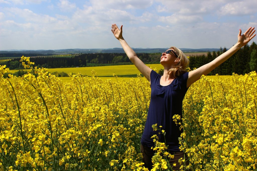Woman in navy blue blouse, standing in field of yellow flowers, arms raised, grateful smile on her face