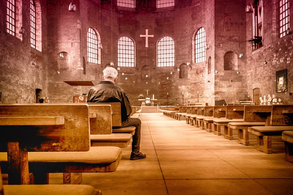 The Best Thing About Surrendering to God's Will_rear view of older man sitting in a stone church